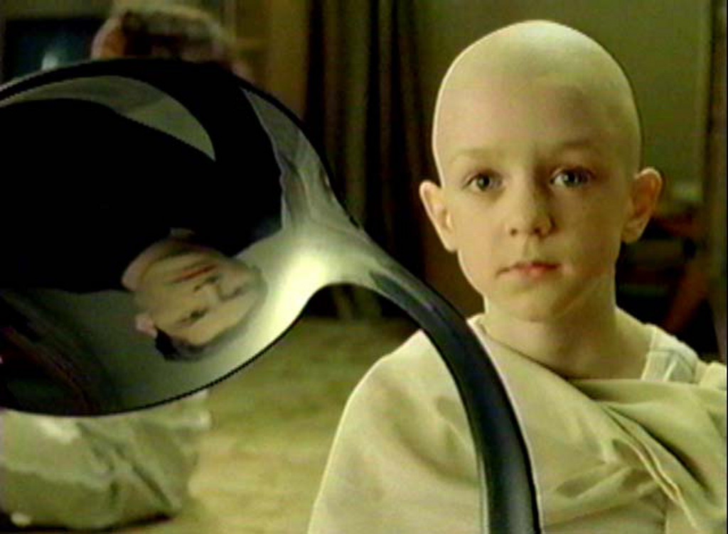 A bended spoon which mirror Neo's face, with a young monk in the foreground